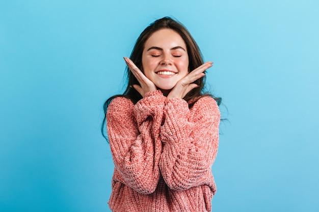 Close-up portret van schattige brunette lachend met gesloten ogen. meisje in roze trui raakt zachtjes haar wangen.