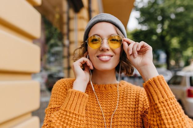 Close-up portret van schattige europese dame met naakt make-up luisteren muziek tijdens het lopen op straat in herfstdag