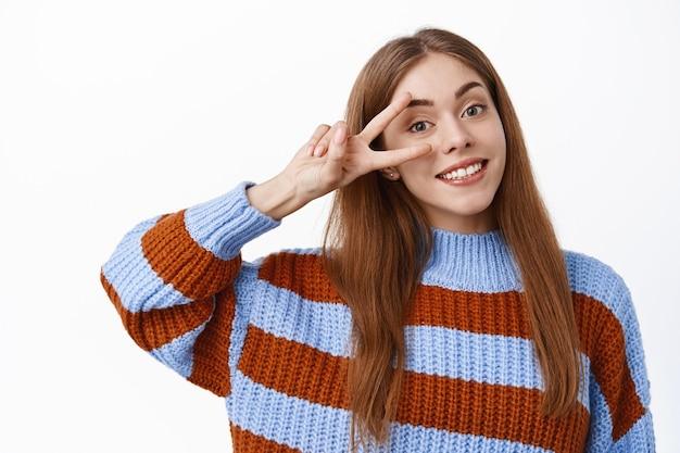 Close-up portret van schattige jonge vrouw die vredesteken boven oog toont, glimlacht en er gelukkig uitziet, zich gezond en positief voelt, in trui tegen witte muur staat