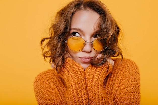 Close-up portret van schattige peinzende vrouw met glanzende krullen wegkijken op gele achtergrond