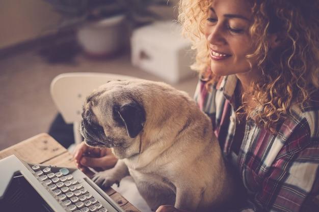 Close-up portret van schattige vrouw die lacht en probeer te schrijven met oude typemachine bu hond pug grap en geniet van de liefde en vriendschap die haar werk verstoren