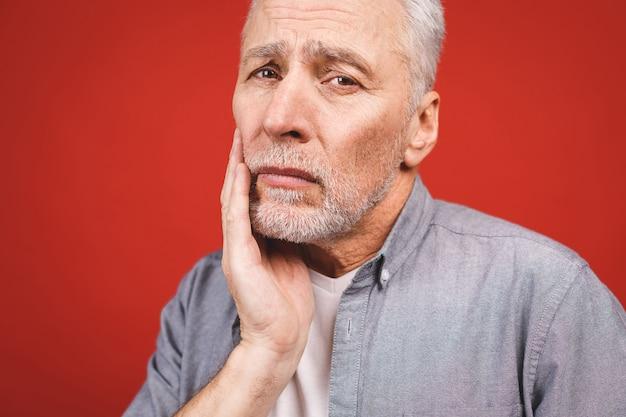 Close-up portret van senior bejaarde man die lijden aan kiespijn