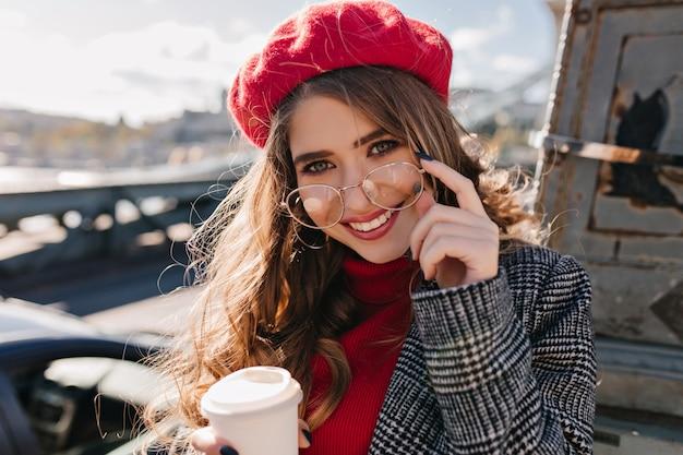 Close-up portret van sensuele bruinharige vrouw met kop warme drank poseren in koude dag