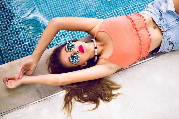 Close-up portret van sensuele glamour model krijgen zonnebaden in de buurt van privé zwembad
