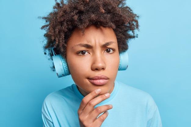 Close-up portret van serieus afro-amerikaans meisje houdt hand op kin ziet er ontevreden gekleed nonchalant luistert muziek via koptelefoon of leert nieuwe buitenlandse woorden geïsoleerd over blauwe muur