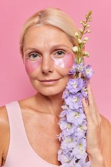 Close-up portret van serieuze vijftig jaar oude vrouw brengt hydrogel patches aan onder de ogen kijkt direct naar de camera houdt bloemen heeft een schone gezonde huid ondergaat schoonheidsprocedures poses binnen.