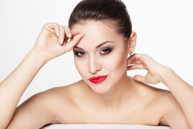 Close-up portret van sexy blanke jonge vrouw model met glamour rode lippen, lichte make-up, oogpijl make-up, zuiverheid teint. perfect schone huid.
