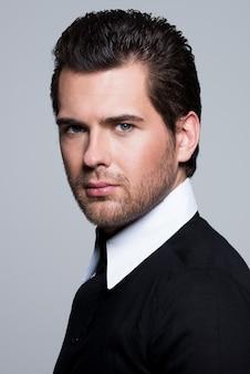 Close-up portret van sexy jonge man in zwart shirt vormt over grijze muur.
