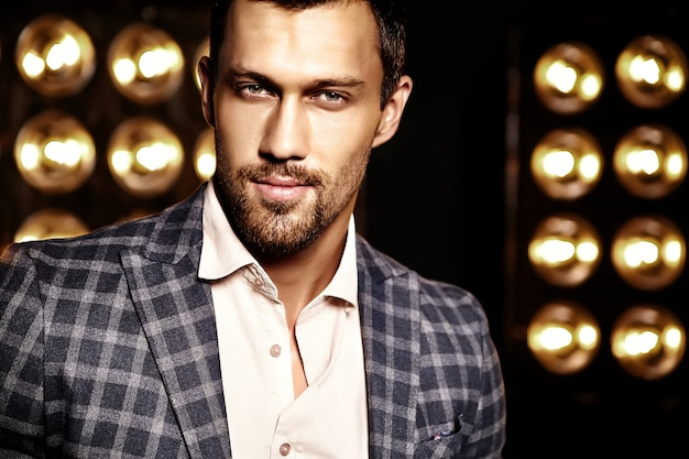 Close-up portret van sexy knappe mode mannelijk model man gekleed in elegant pak op zwarte studio lichten achtergrond