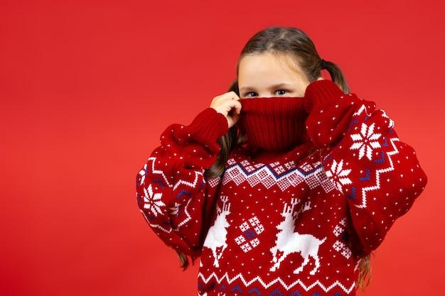Close-up portret van speels meisje verbergen half gezicht in rode kerst trui met rendieren geïsoleerd...