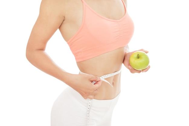 Close-up portret van sportieve vrouw maatregelen haar taille met een meetlint terwijl groene appel
