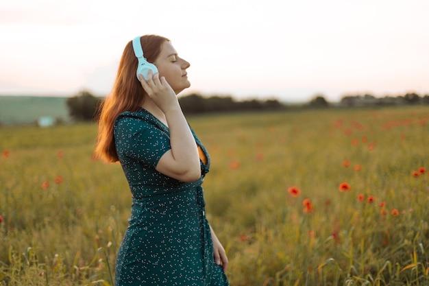 Close-up portret van stijlvol jong meisje mediteert met witte draadloze koptelefoon buiten in een stadspark