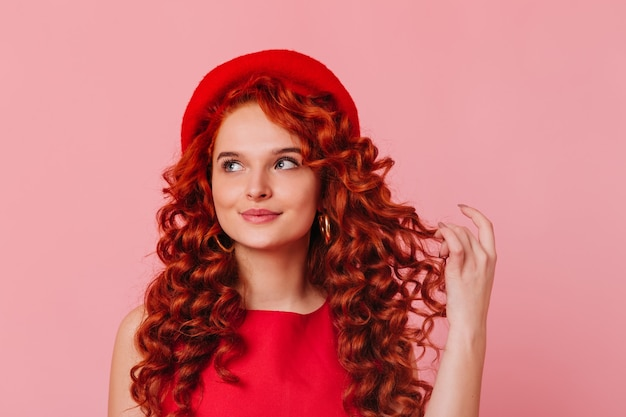 Close-up portret van stijlvolle jongedame in rode baret en top blueeyed meisje raakt dromerig haar rode krullen op roze achtergrond close-up portret van stijlvolle jongedame in rode baret en top