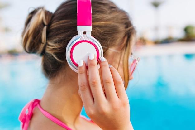 Close-up portret van stijlvolle meisje met schattig kapsel rusten in het blauwe buitenzwembad in zonnige dag