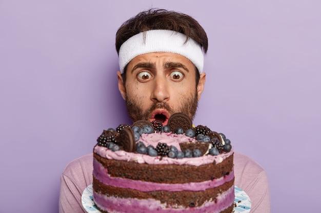 Close-up portret van stomverbaasde man staart met afgeluisterde ogen naar heerlijke zoete cake, heeft een groot verlangen om een smakelijk dessert te eten, houdt zich aan een dieet en gaat sporten, draagt een witte hoofdband