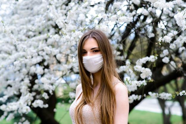 Close-up portret van teder meisje in een witte blouse onder een bloeiende kersenboom met een masker met bloemen op van het coronavirus.