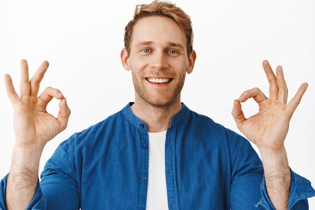Close-up portret van tevreden roodharige man, glimlachend en gelukkig kijkend, ok oké gebaar tonend om iets goeds te prijzen, goed gedaan geweldig gebaar, uitstekende service aanbevelend, witte muur