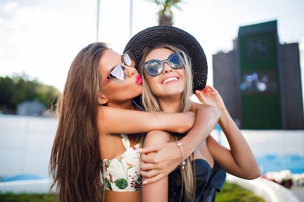 Close-up portret van twee aantrekkelijke blonde en brunette meisjes met lang haar poseren voor de camera in de stad. het ene meisje knuffelt het andere.
