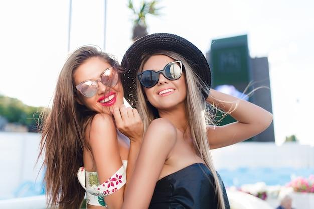 Close-up portret van twee aantrekkelijke blonde en brunette meisjes met lang haar poseren voor de camera in de stad. ze glimlachen naar de camera.