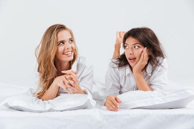 Close-up portret van twee gelukkige mooie vriendinnen die samen op het bed liggen met kussens
