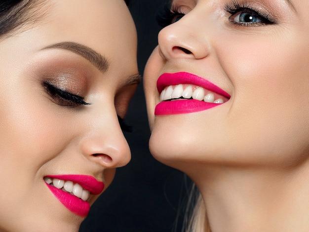 Close-up portret van twee jonge mooie glimlachende vrouwen. helderroze lippenstift. huidverzorging, cosmetica, spa-therapie of cosmetologieconcept