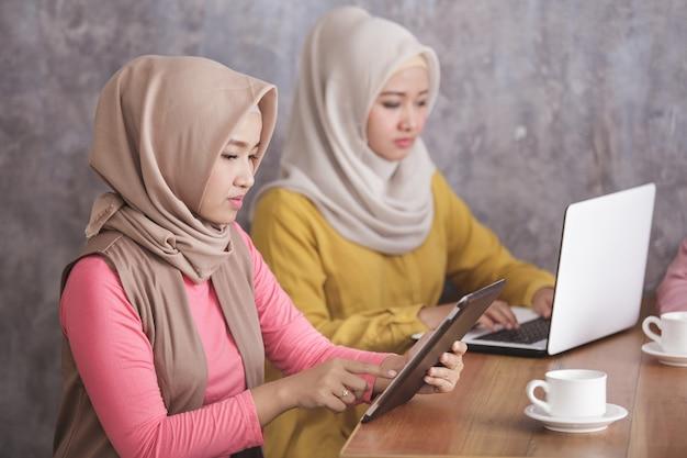 Close-up portret van twee vrouwen die hijab dragen bezig zijn met hun eigen gadget