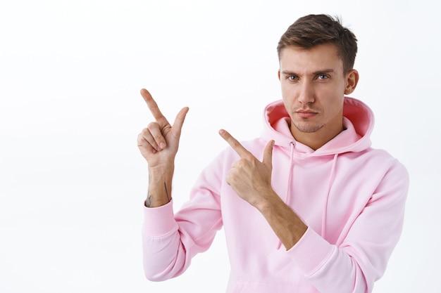 Close-up portret van vastberaden, nadenkende jonge zelfverzekerde man met blond haar, roze hoodie moedig aan om even de tijd te nemen, de site te bezoeken en informatie te leren, de weg te wijzen, de camera te kijken en de linkerbovenhoek te richten