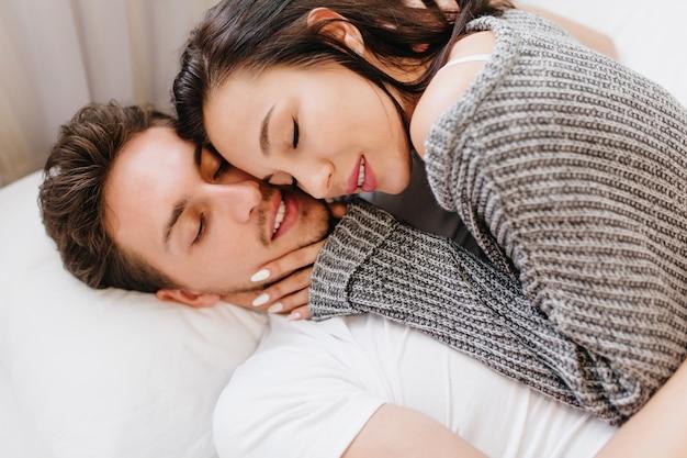 Close-up portret van verbazingwekkende brunette vrouwelijke model liggend in bed met echtgenoot in wit t-shirt