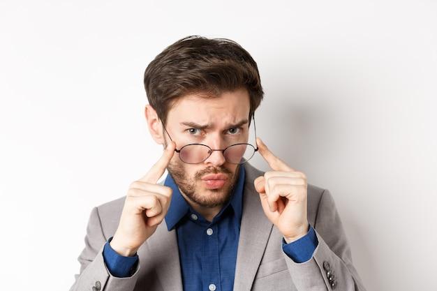 Close-up portret van verdachte man in pak, bril opstijgen en fronsen met aarzelend gezicht, staande op een witte achtergrond.