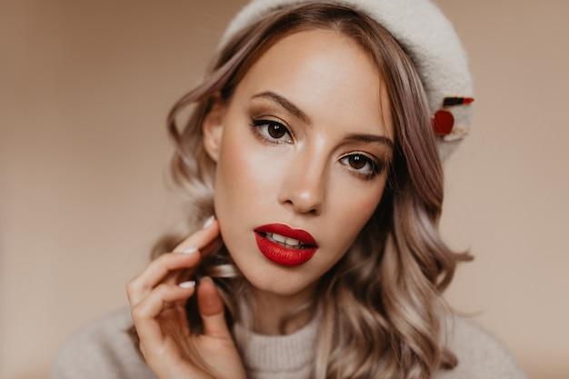 Close-up portret van verfijnde mooie vrouw geïsoleerd op bruine muur