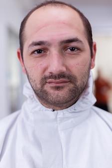 Close-up portret van vermoeide arts die een veiligheidspak draagt en naar de camera kijkt tijdens de wereldwijde pandemie met coronavirus