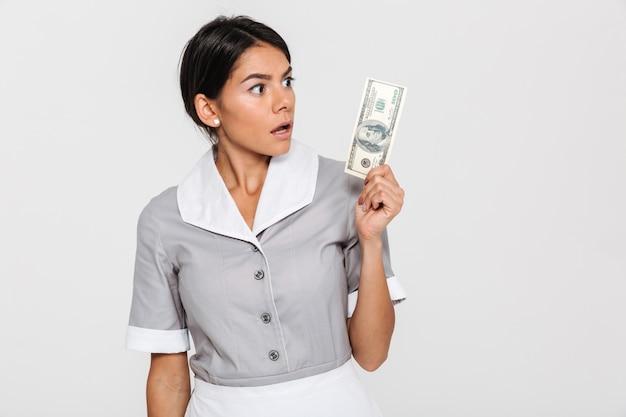 Close-up portret van verrast jonge vrouw in uniform houden honderd dollar biljet