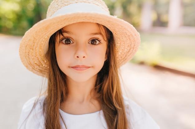 Close-up portret van verrast kind met grote glanzende bruine ogen poseren. geweldig klein meisje in trendy zomerhoed permanent op de weg in zonnige dag.