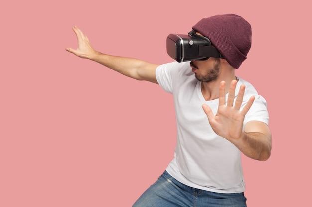 Close-up portret van verraste bebaarde jonge hipster man in wit overhemd en casual hoed staande, vr speelspel dragen met opgeheven armen. binnen, geïsoleerd, studio-opname, roze achtergrond