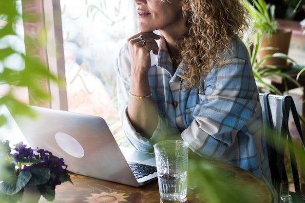 Close-up portret van volwassen vrouw die werkt en laptopcomputer gebruikt die thuis of in de winkel aan tafel zit - concept van moderne technologie verbindingslevensstijl - freelance externe werknemer mensen