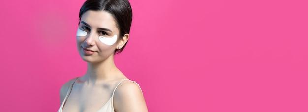 Close-up portret van vrij aantrekkelijk meisje met blote schouders met behulp van patches onder de ogen