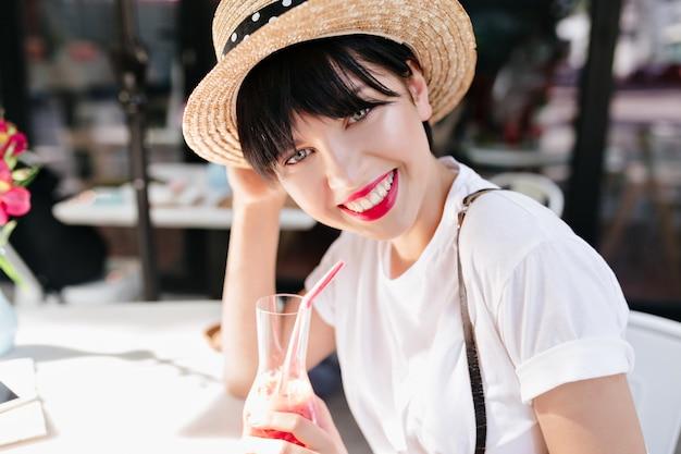 Close-up portret van vrolijk meisje met grote grijze ogen en donker kort haar glimlachend en sap drinken