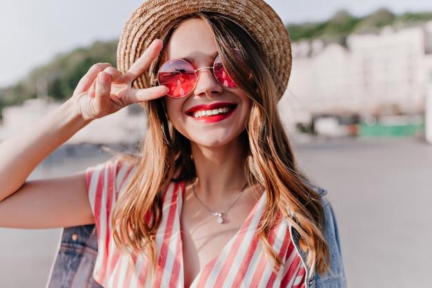 Close-up portret van vrolijke blonde vrouw in stijlvolle roze zonnebril. prachtig kaukasisch meisje dat positieve emoties uitdrukt in zomerdag.