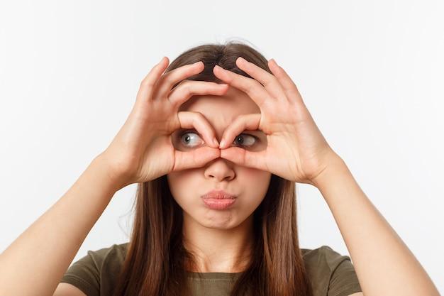 Close-up portret van vrolijke, leuke, stijlvolle, aantrekkelijke, trendy meisje verrekijker met vingers maken, geïsoleerd op grijze achtergrond, goed humeur