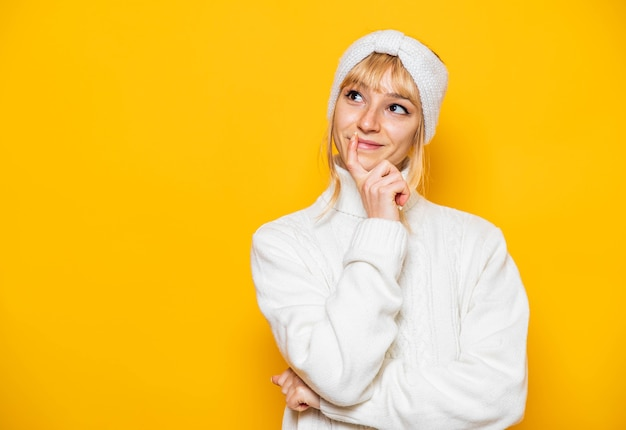Close-up portret van vrolijke mooie jonge vrouw denken poseren in witte comfortabele kleding geïsoleerd op helder gele achtergrond Premium Foto