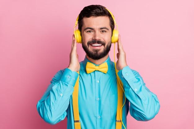 Close-up portret van vrolijke zelfverzekerde blije man luisteren muziek in oortelefoons