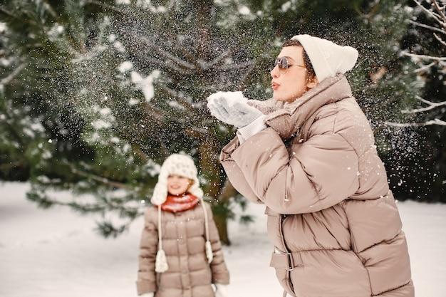 Close-up portret van vrouw in bruine jas in besneeuwde park met haar dochter