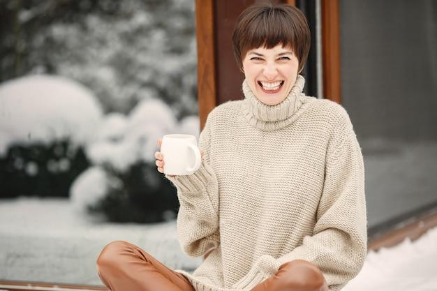 Close-up portret van vrouw in witte trui, het drinken van thee