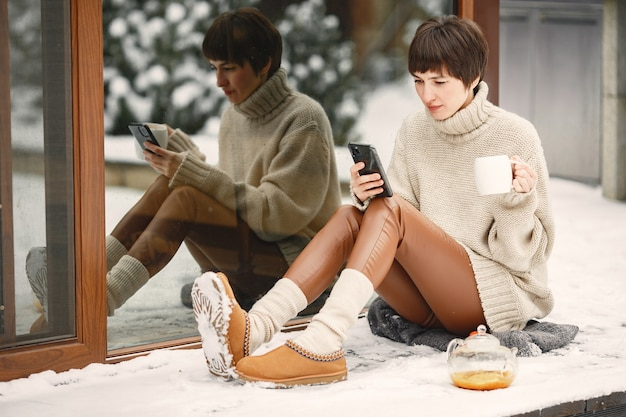 Close-up portret van vrouw in witte trui, thee drinken en smartphone te houden