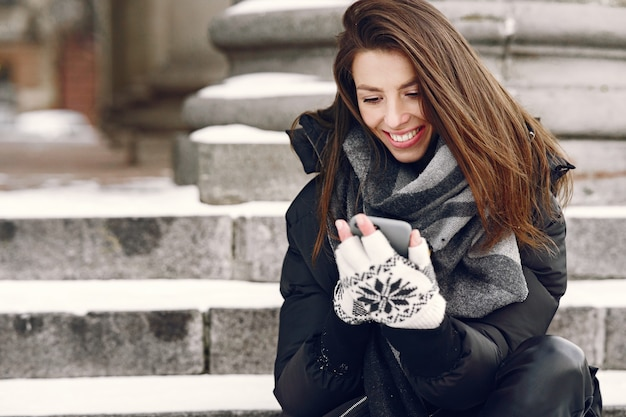 Close-up portret van vrouw in zwarte jas kijken naar video op de trap
