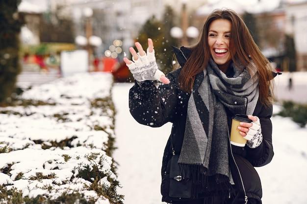 Close-up portret van vrouw in zwarte jas koffie drinken