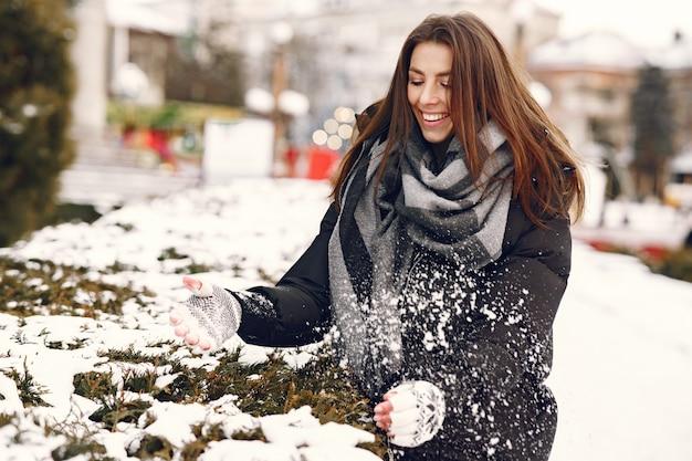 Close-up portret van vrouw in zwarte jas spelen met de sneeuw