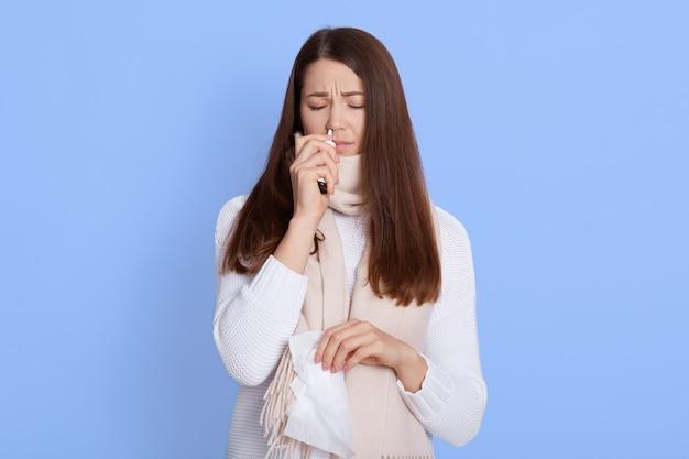 Close-up portret van vrouw met behulp van neusspray geïsoleerd dan blauw