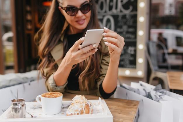 Close-up portret van vrouw met gebruinde huid sms-bericht tijdens de lunch op terras