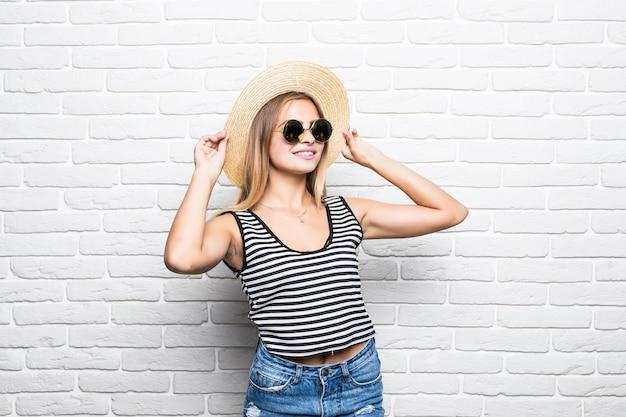 Close-up portret van vrouw poseren trendy strooien hoed en zonnebril tegen witte bakstenen muur.